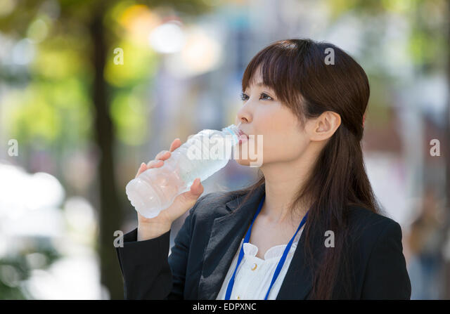 Businesswoman Drinking Bottled Water - Stock Image