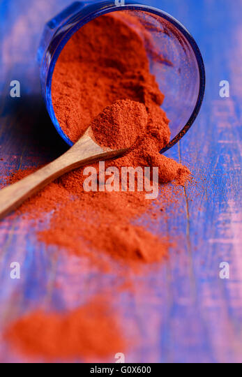 Ground paprika in a blue glass on wooden spoon - Stock Image