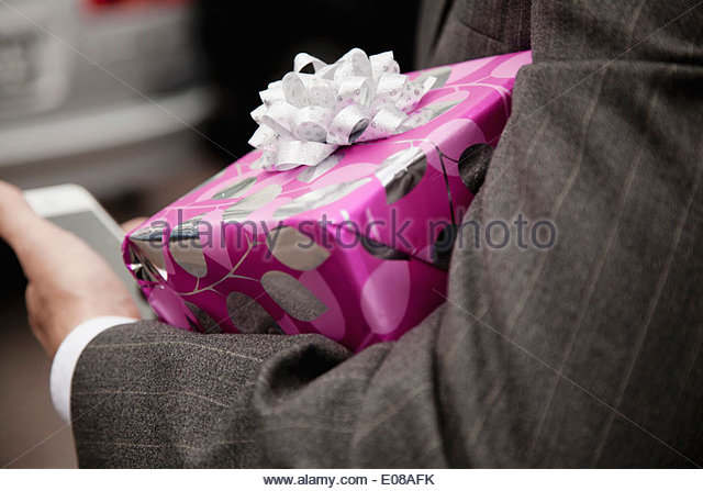 Cropped image of man holding gift box outdoors - Stock Image