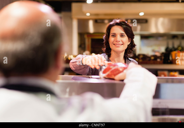 Woman buying meat from butcher - Stock Image