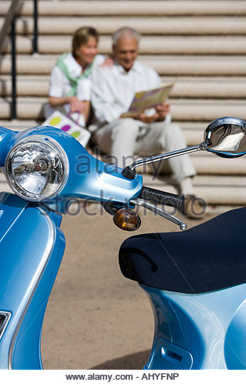 Senior couple sitting on urban steps looking at street map focus on blue motor scooter parked in foreground - Stock Image