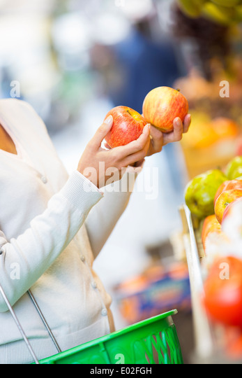 Female close-up hand apple orange grape - Stock Image