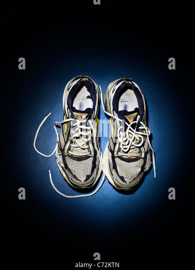 Old running shoes, trainers in a spotlight - Stock Image