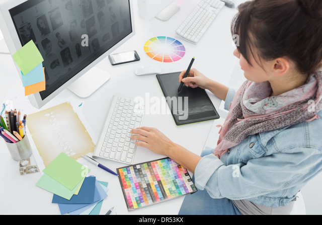 Artist drawing something on graphic tablet at office - Stock Image