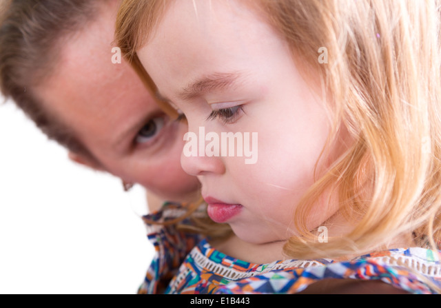 Protective mother watching over her little daughter with the pretty little girl in profile to the camera with downcast - Stock Image