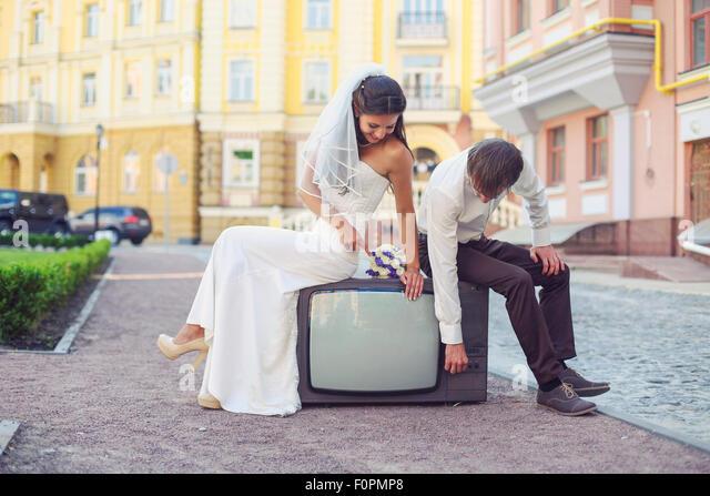 'Happy newlyweds sitting on retro tv set outdoors - Stock Image