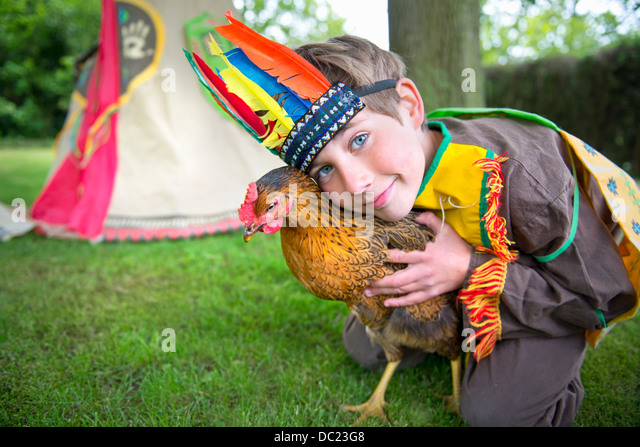 Boy dressed in Native American costume holding chicken, portrait - Stock-Bilder