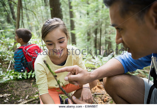 Father showing daughter stick in woods - Stock Image