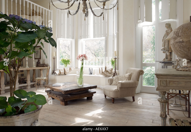 White open plan interior with potted plant, large windows and mezzanine - Stock Image
