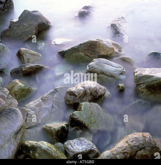 Rocks with sea moving around them - Stock Image