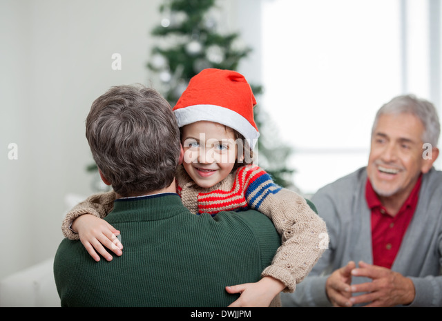 Happy Boy Embracing Father During Christmas - Stock Image