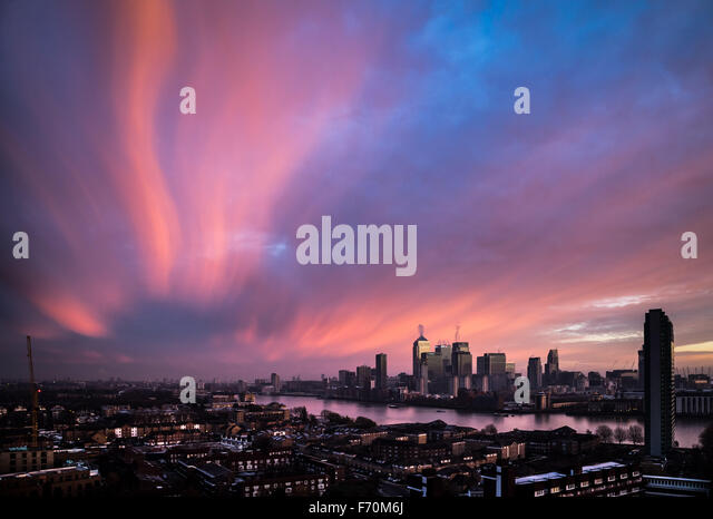 London, UK. 23rd November, 2015. UK Weather: cold air brings dramatic morning light sunrise over Canary Wharf business - Stock Image