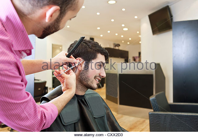 A male hairdresser cutting his male clients hair with scissors - Stock Image