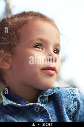 Beautiful little girl looks into the distance. - Stock Image