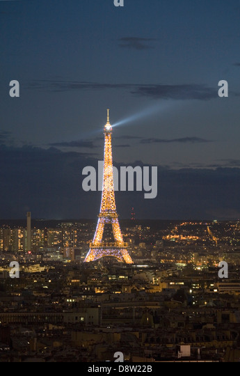 Eiffel Tower lit up at night, with rotating searchlight on top, seen from Montmartre, Paris, France - Stock Image