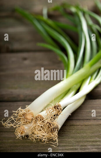 Bundle of fresh scallions on a wooden board - Stock Image