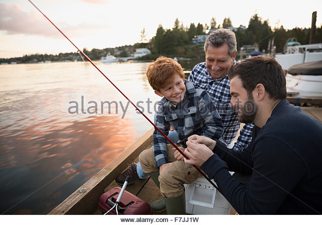 Multi-generation family preparing fishing lake dock sunset - Stock Image