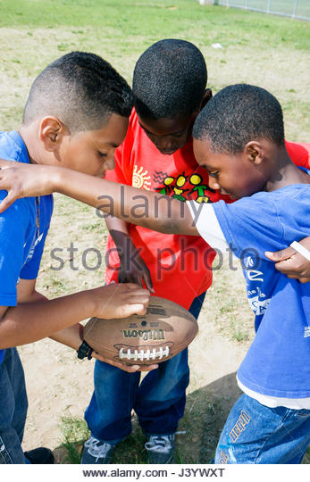 Miami Florida Moore Park touch football huddle sport game strategy Hispanic Black boy boys child student playground - Stock Image