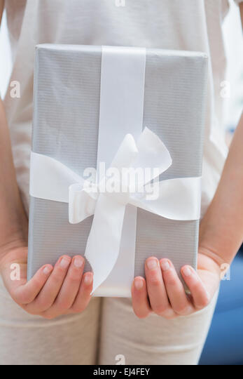 Daughter hiding presenting behind back - Stock Image