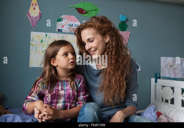 Portrait of woman with her little daughter in children's room - Stock Image