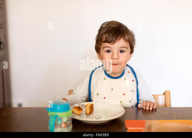 cheeky boy sitting at table eating snack - Stock Image