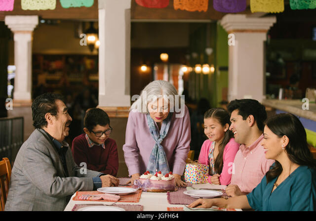 Older woman blowing out candles on birthday cake in restaurant - Stock Image
