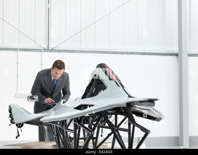 Automotive designer inspecting part-built supercar in car factory - Stock-Bilder