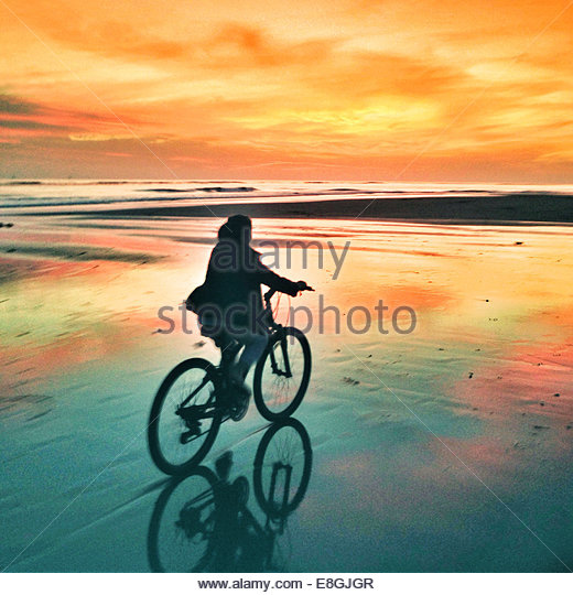Silhouette of a woman cycling along the beach at sunset - Stock Image