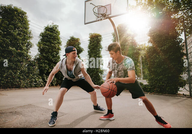 Teenage friends playing streetball against each other and having fun. Two young men having a game of basketball - Stock Image