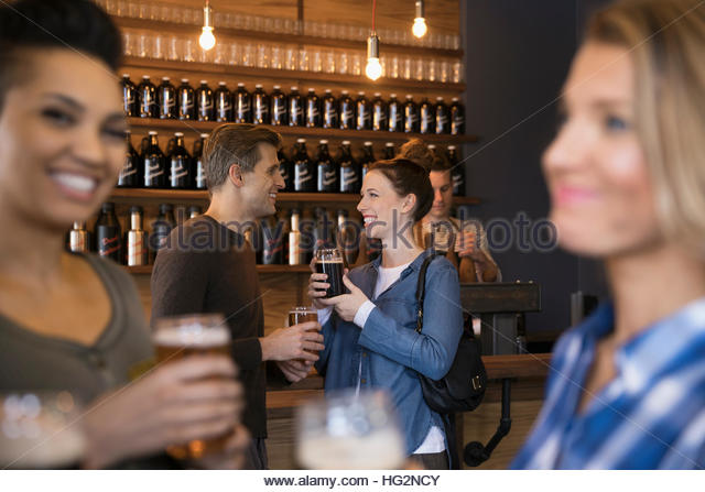 Smiling couple talking and drinking beer in brewery tasting room - Stock Image