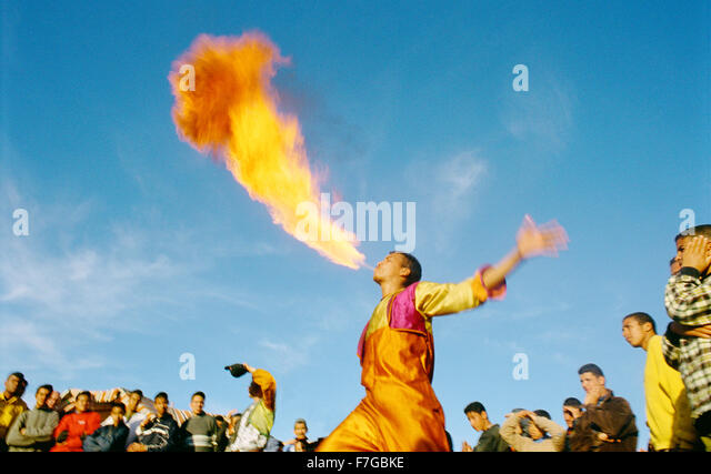 A fire breather spits fire at Jema al-Fna as a crowd looks on. Marrakech, Morocco, North Africa - Stock Image