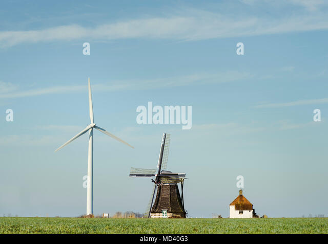Modern wind turbine and traditional Dutch windmill stand together, Workum, Friesland, Netherlands - Stock Image