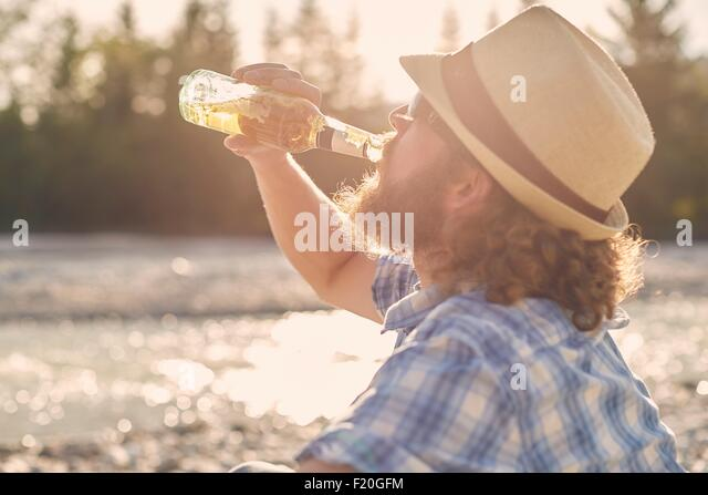 Side view of mid adult man wearing hat drinking beer from beer bottle - Stock Image