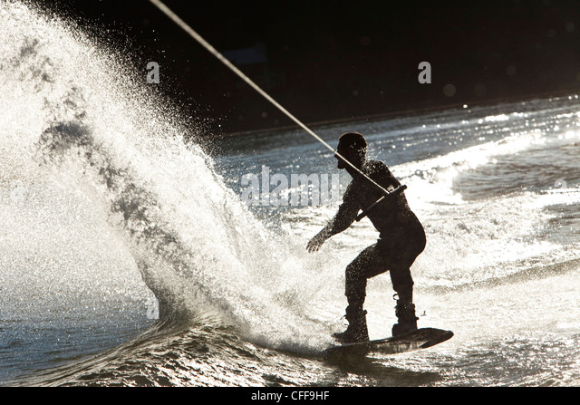 A professional wakeboarder carves and slashes on a lake at sunset in Idaho. - Stock Image