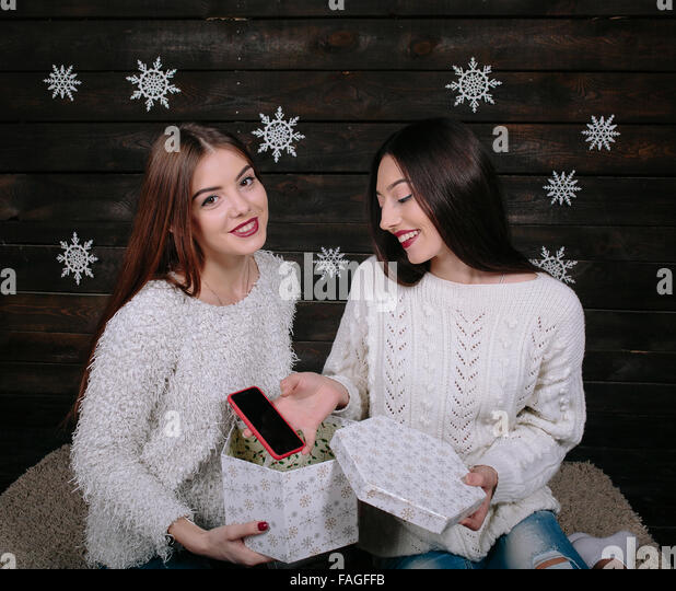 Two young girls holding holiday present - Stock Image