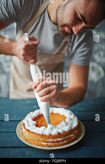 Baker decorating tasty cake with whipped cream - Stock Image