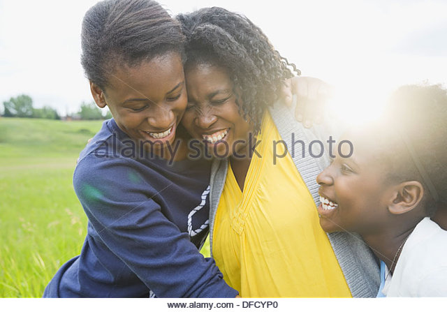 Cheerful mother and daughters hugging outside - Stock-Bilder