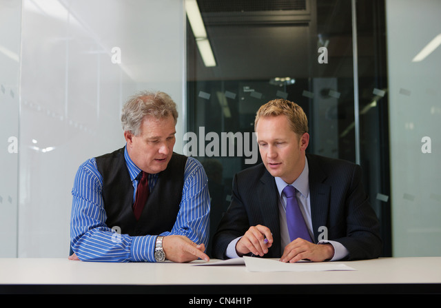 Manager sitting in office with businessman - Stock Image