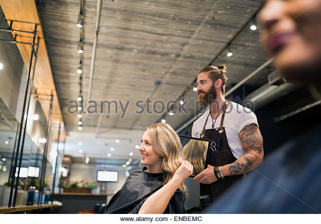 Hairstylist showing woman hair with mirror hair salon - Stock-Bilder