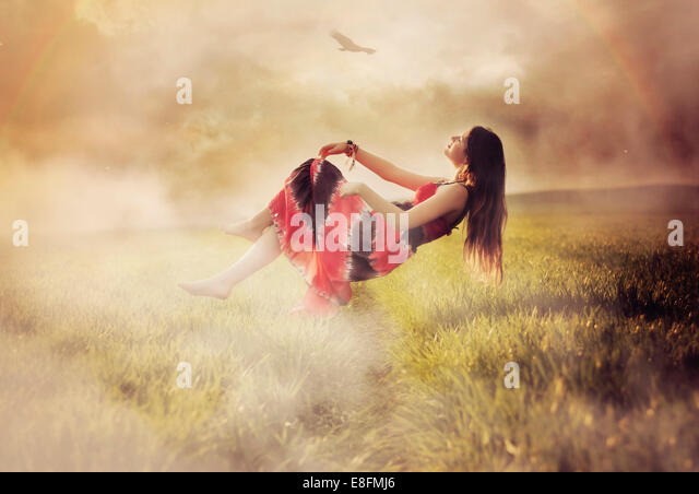 Woman floating over a meadow, Poland - Stock Image