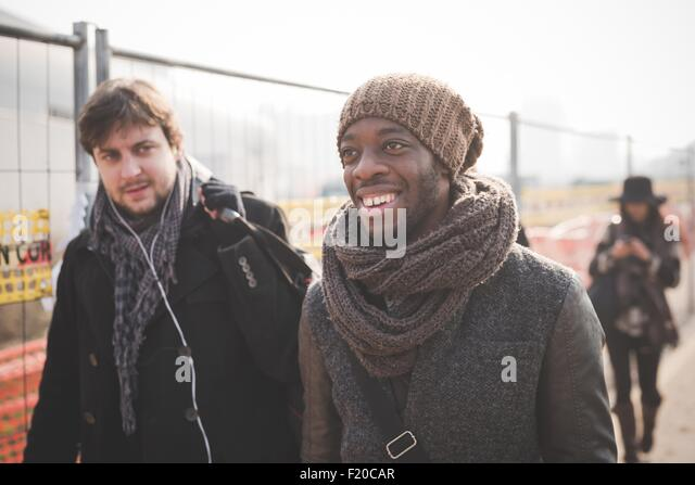 Young male friends strolling in park - Stock Image