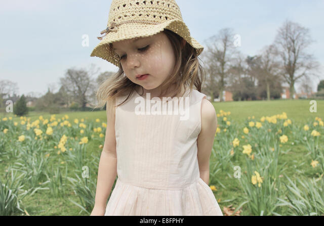 Girl wearing a straw hat standing in a field - Stock Image