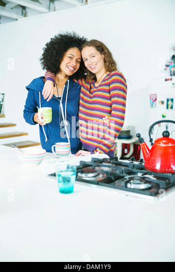 Women hugging in kitchen - Stock Image