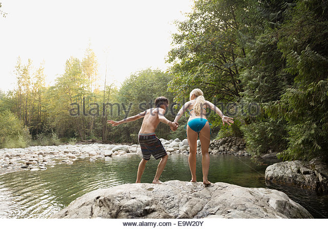 Couple holding hands and jumping from rock - Stock Image