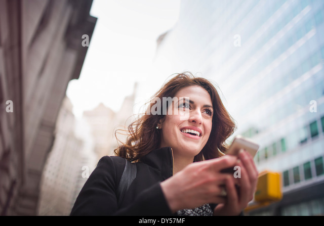 Young woman holding cellphone, New York, USA - Stock Image