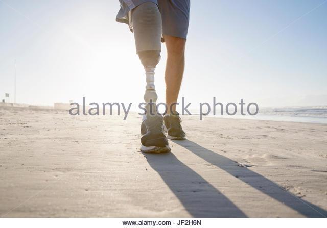 Close Up Of Man With Artificial Leg Running Along Beach - Stock Image