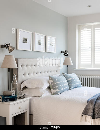 Mimosa upholstered buttoned headboard by Loaf in bedroom with cushions by John Lewis. The small pewter wall lights - Stock Image