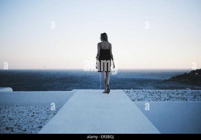 Rear view of woman looking out to sea - Stock-Bilder