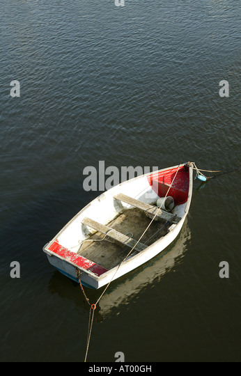 single white and red rowing boat from above with expanse of water - Stock Image