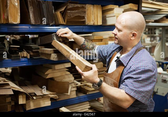 Guitar maker selecting wooden block in workshop - Stock Image